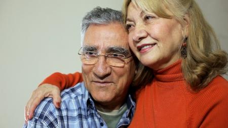 Senior couple sitting on sofa photo