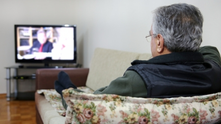 Senior man watching TV show while sitting on sofa in his living room