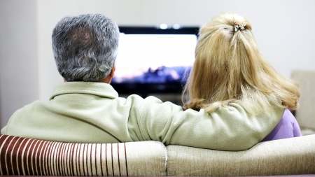 Senior couple sitting together on sofa, watching television