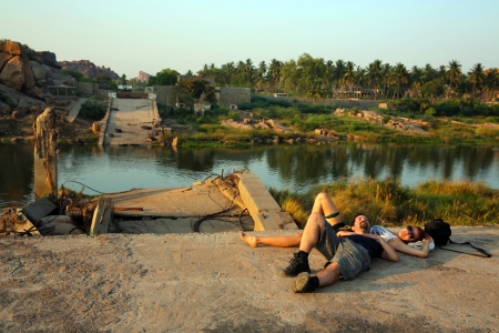 Tourists couple lying down by ruined bridge over calm river