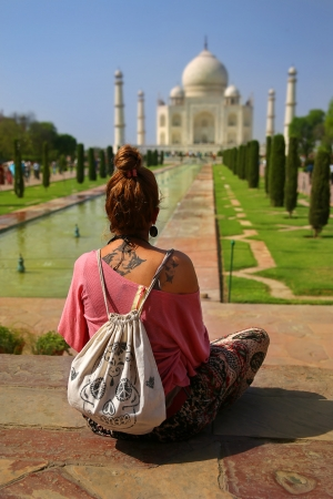 Caucasian woman sitting on bench and looking to Taj Mahal Stockfoto