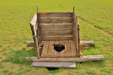 Mongolian wooden squat toilet outside yurt, grassland of mongolia Фото со стока