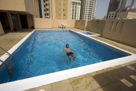 middle eastern clothes: man swim in swimming pool at roof of apartment, bahrain Stock Photo