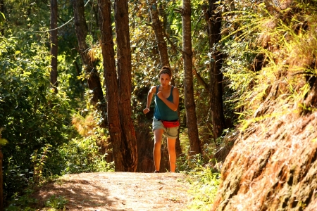 Sexy girl running along narrow footpath in forest photo