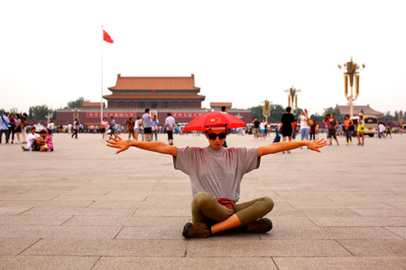 Female tourist wearing hat with chinese flag making funny faces at Beijing, China
