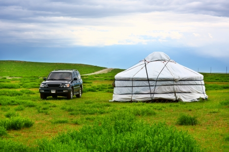 ger: Modern jeep parked next to traditional Mongolian yurt