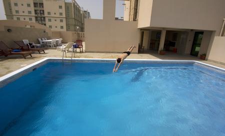man swim in swimming pool at roof of apartment, bahrain Stockfoto