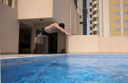 man swim in swimming pool at roof of apartment, bahrain Фото со стока