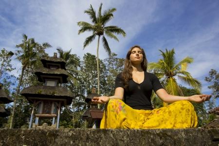 caucasian woman meditating yoga in balinese temple