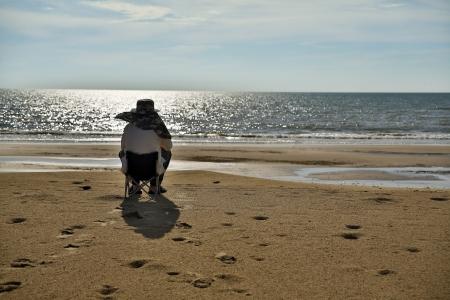 Senior man sitting at beach watching sunset