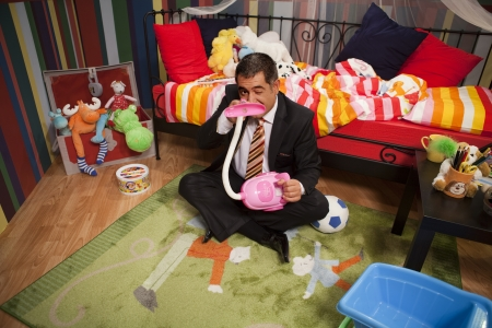 Mature man in full suit playing in children bedroom - Childish - Humour
