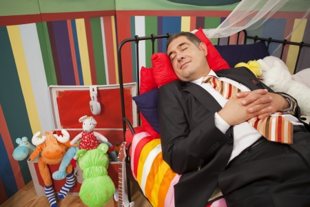 toy truck: Mature man wearing full suit sleeping happly in childrens bed - Relaxation - Humour -  Childish