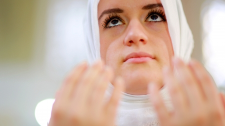 Muslim girl saying her everyday salat prayer in mosque Фото со стока