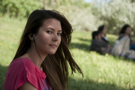 Young woman listening to music on grass at University campus with friends in background
