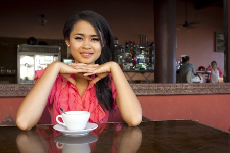 gorgeous asian woman in cafe, drinking coffee, tea