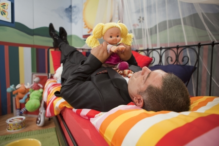 Mature man in full suit playing in children;s bedroom - Childish - Humour