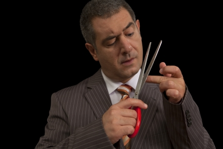 Businessman wearing suit, cutting nails with huge scisors - Humour - Bodycare