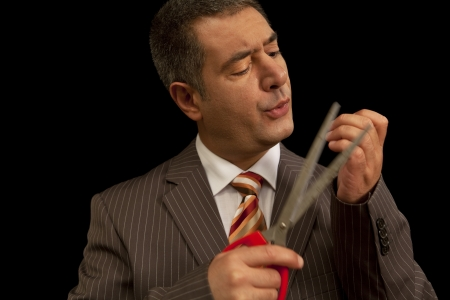 raised eyebrow: Businessman wearing suit, cutting nails with huge scisors - Humour - Bodycare  Stock Photo