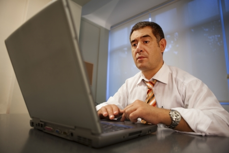 Businessman working on laptop in office environment