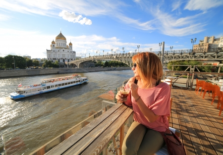 moskva river: woman drinking cocktail at a club, moskow view on background with Cathedral of Christ the Saviour, Moskva River and daily city life