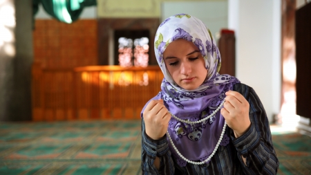 Muslim girl saying her everyday salat prayer in mosque photo