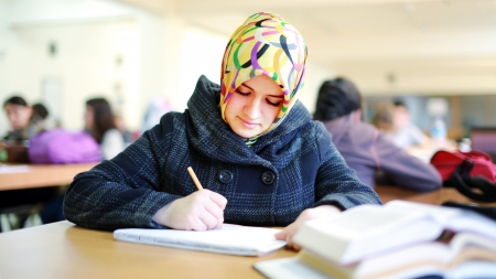Muslim female student reading book in library photo