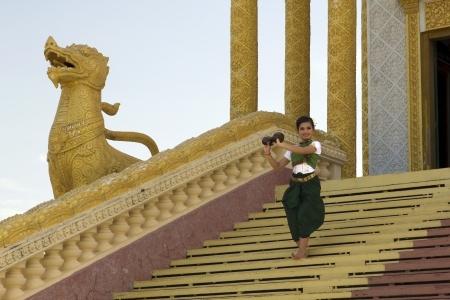 Beautiful Asian Girl performs coconut folk dance in temple