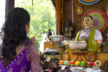 Asian girl praying in temple, wat, pagoda, Phnom Penh, Cambodia