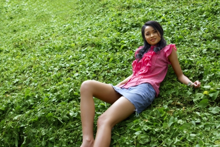 Sexy erotic asian girl with mini skirt on green grass