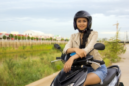 sexy asian girl with mini skirt, helmet, motorcycle in cambodia
