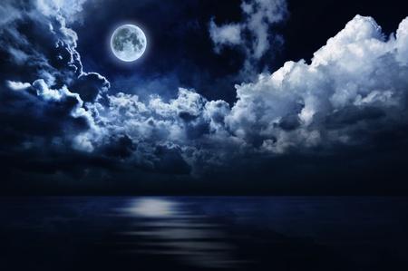 noche y luna: Luna llena en el cielo nocturno sobre el agua