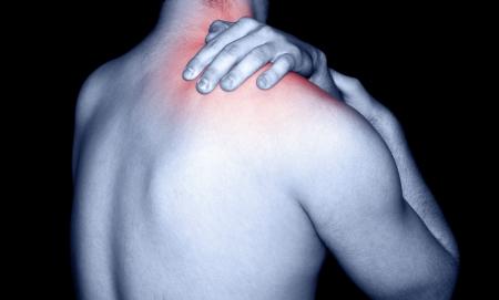 dolor muscular: El hombre masajes a un dolor en el hombro Foto de archivo