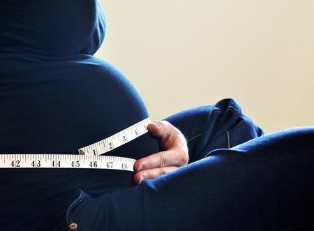 maternal: Woman measuring her waist size