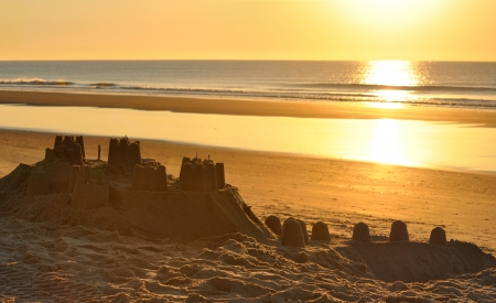 Big sand castle on the beach at evening photo