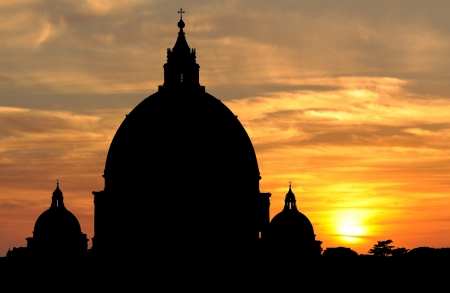 Silhouette of the huge domes of Saint Peters Basilica breaking the skyline at sunset in Vatican City, Rome Stock Photo