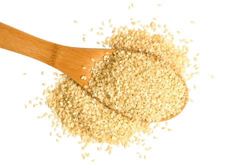 white sesame seeds: Big scoop of sesame seeds over a white background. Stock Photo