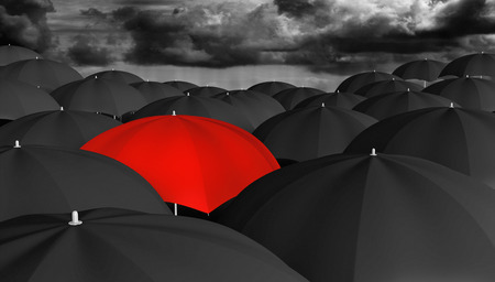 Individuality and thinking different concept of a red umbrella in a crowd of black ones