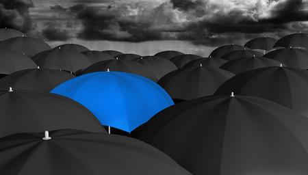 Leiderschap en innovatie concept van een blauwe paraplu in een menigte van zwarte degenen