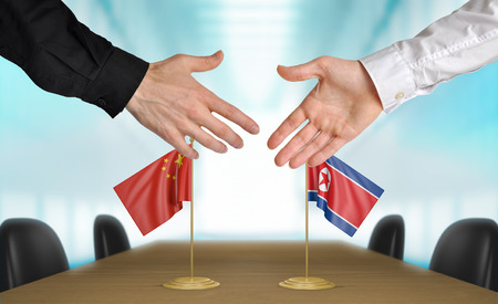 agreeing: China and North Korea diplomats agreeing on a deal