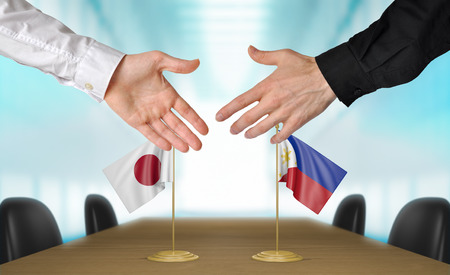 agreeing: Japan and Philippines diplomats agreeing on a deal Stock Photo