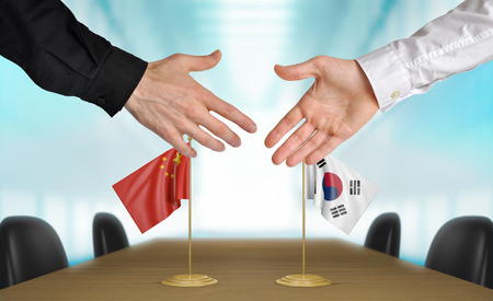 agreeing: China and South Korea diplomats agreeing on a deal
