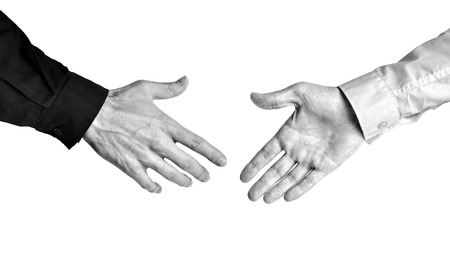 Bold contrast black and white of businessmen showing trust in a deal with a handshake 免版税图像