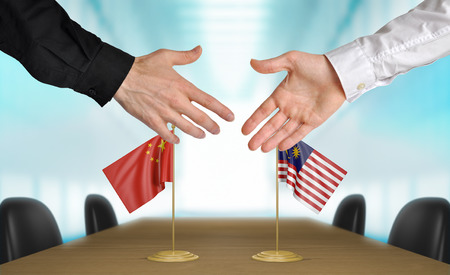 agreeing: China and Malaysia diplomats agreeing on a deal