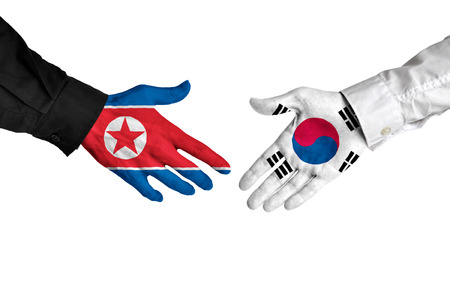 north korea: North Korea and South Korea leaders shaking hands on a deal agreement