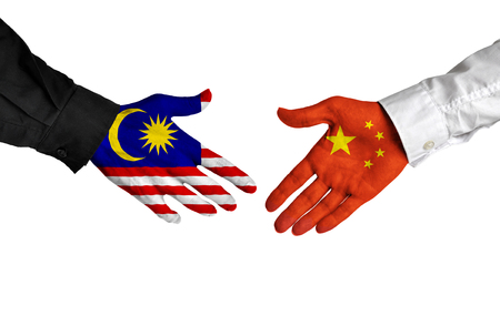 china: Malaysia and China leaders shaking hands on a deal agreement