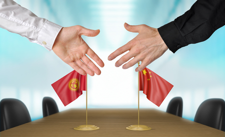 diplomats: Kyrgyzstan and China diplomats agreeing on a deal