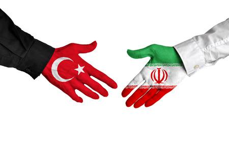pacto: l�deres de Turqu�a e Ir�n d�ndose la mano sobre un acuerdo de reparto Foto de archivo