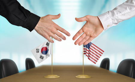 talks: South Korea and United States diplomats shaking hands to agree deal Stock Photo