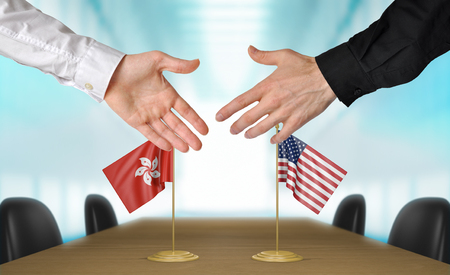 Hong Kong and United States diplomats shaking hands to agree deal