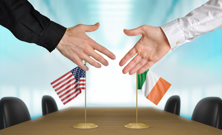 diplomats: United States and Ireland diplomats shaking hands to agree deal